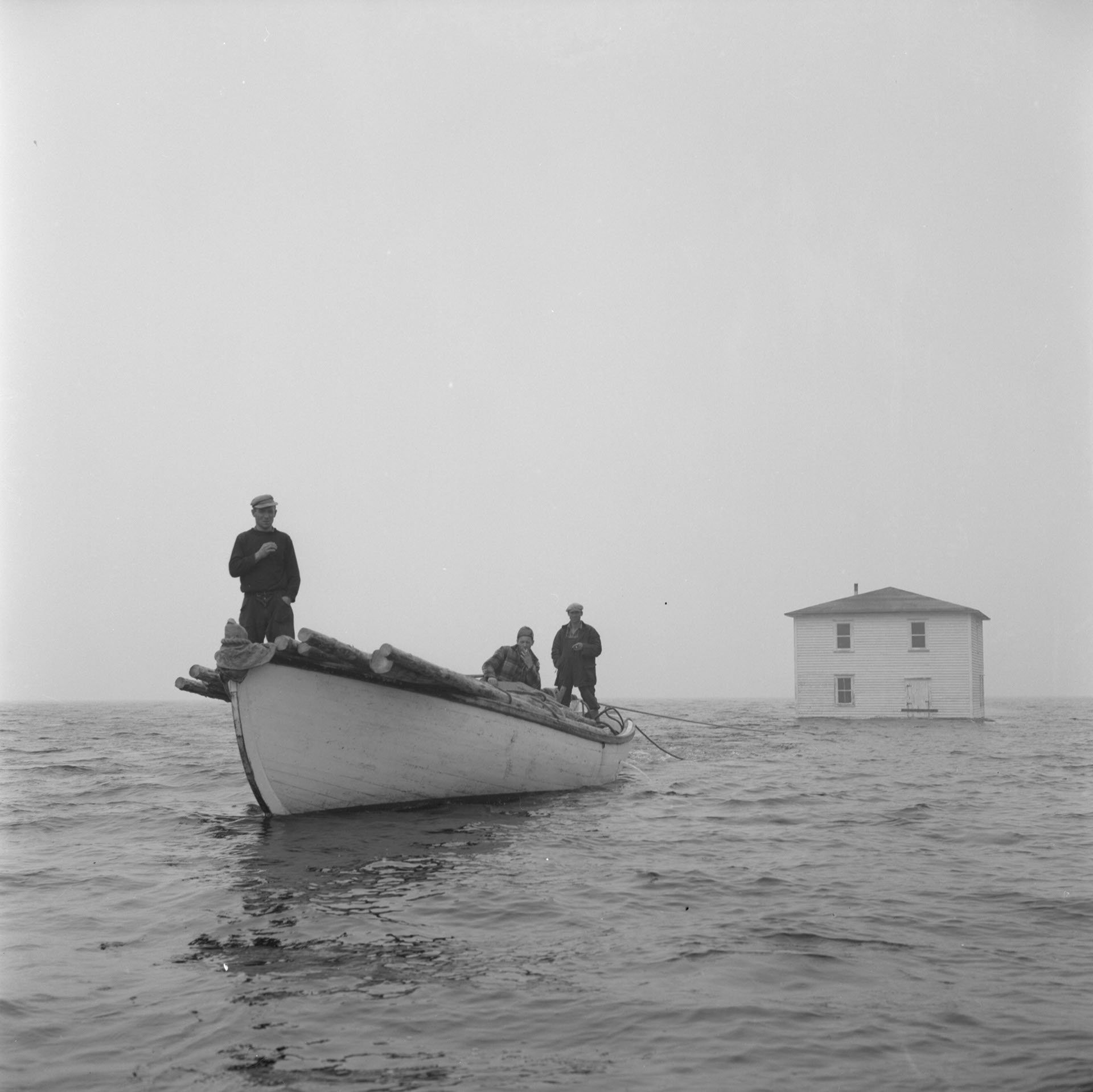 Newfoundland outport house being towed by fishing boat