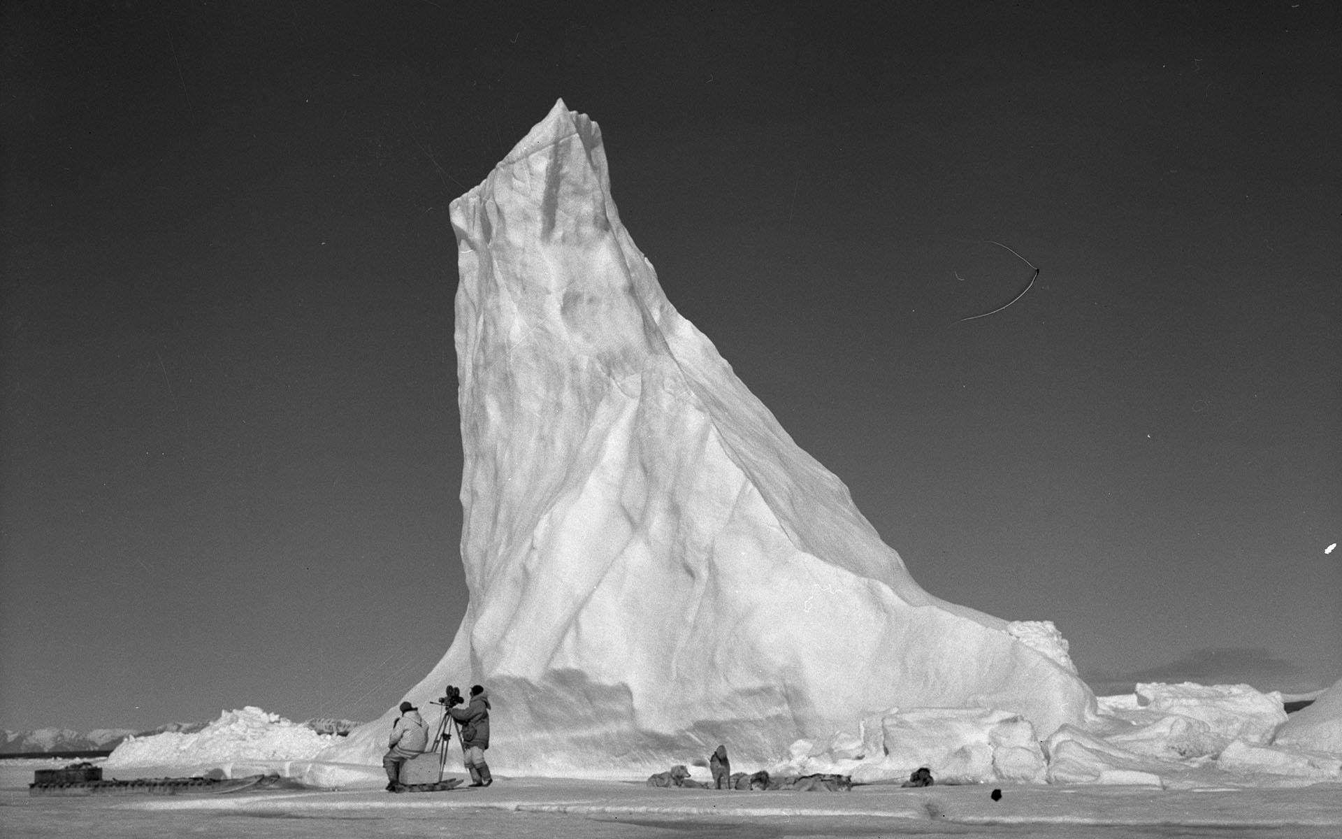 National Film Board crew setting up their camera near a towering arctic iceberg