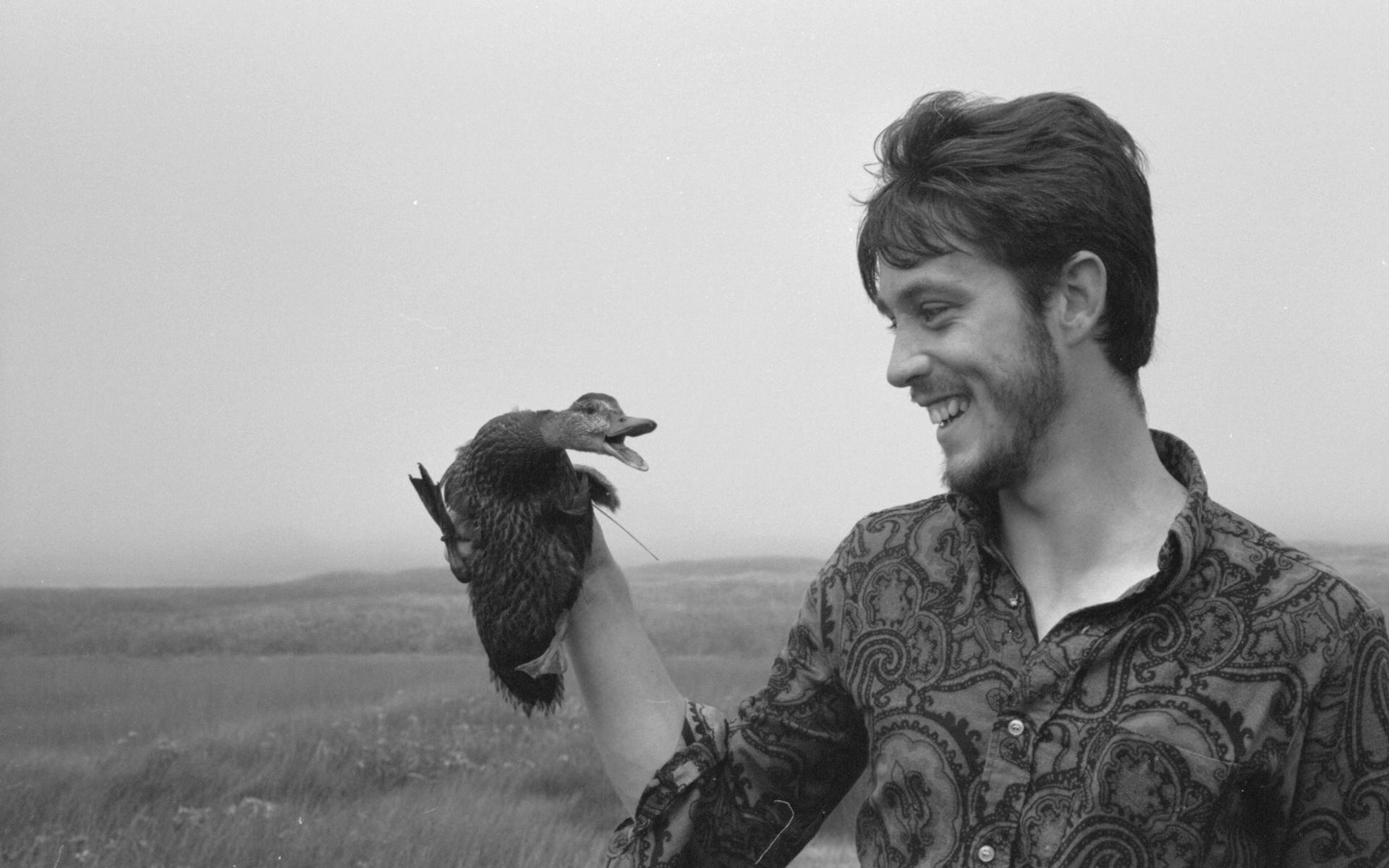 Pierre Norris of the meteorological station placing wild duckling back on nest