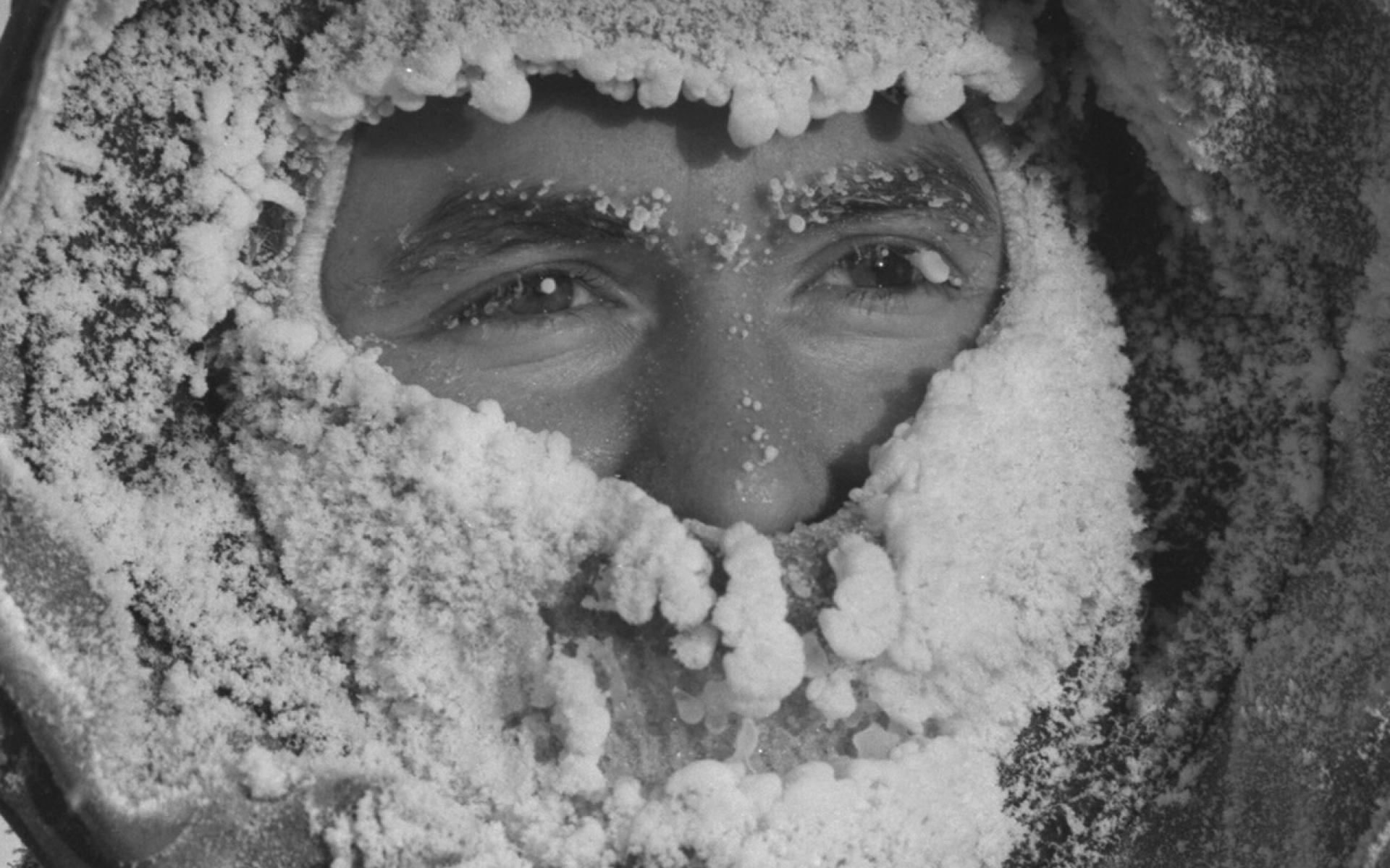 Hydrographer Ralph Courtnage with breath-encrusted parka hood and face-mask while at work out on sea ice