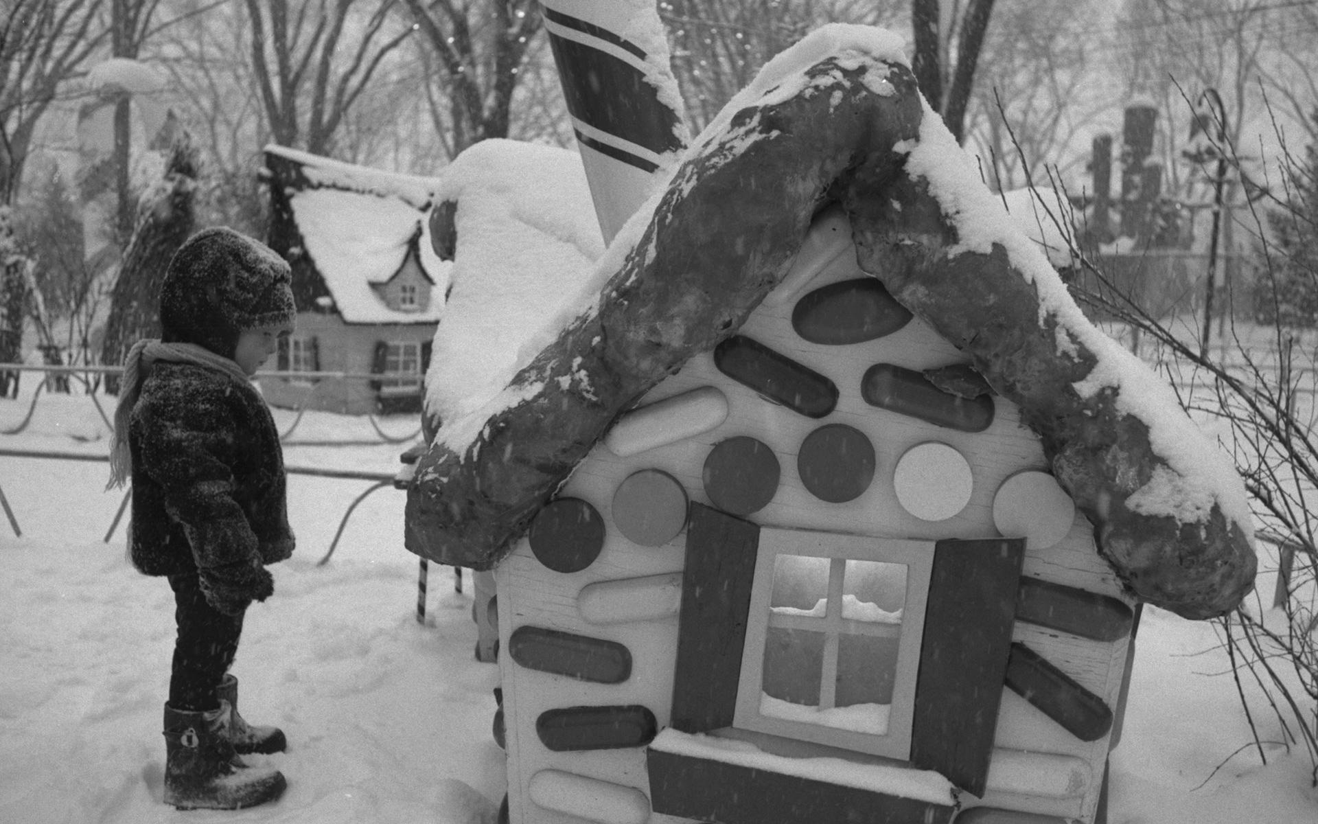 Small child in winter clothing looking at a candy-cane cottage