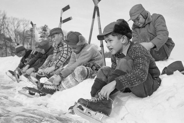 Group of boys sitting on a snowbank, lacing up their hockey skates